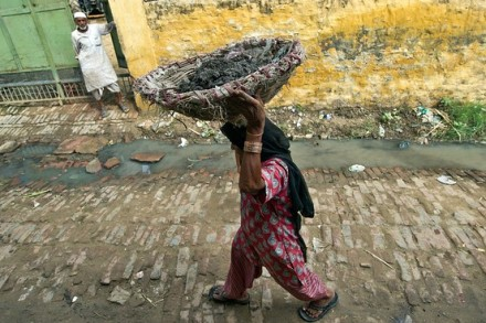 A manual scavenger carried a basket of human excrement after cleaning toilets in the northern village of Nekpur, Uttar Pradesh, Aug. 10, 2012. Agence France-Presse/Getty Images