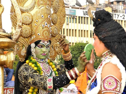 Artist Kali-Maa gets ready as Lord Shiva showing her mirror during the Shri Ram